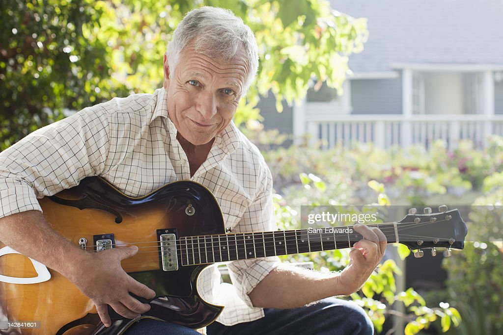 Older man playing guitar outdoors : Stock Photo