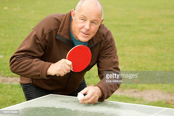 Older man playing ping pong outdoors