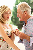 Older Man Proposing To Younger Woman Looking Hopeful