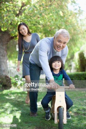 Older man pushing grandson in backyard