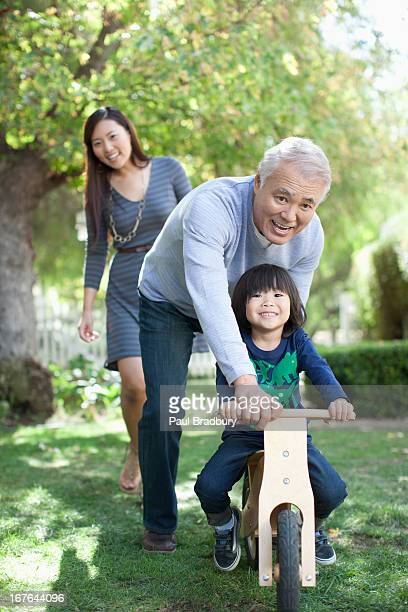 Older man pushing grandson in backyard