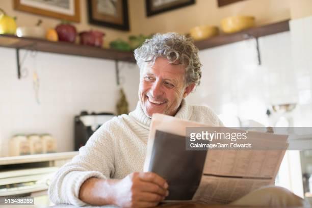 Older man reading news paper in kitchen