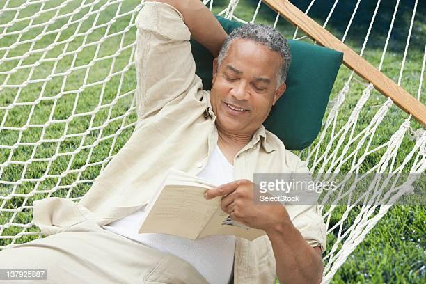 Older man reading on a hammock