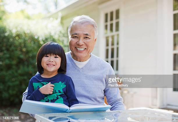 Older man reading with grandson outdoors