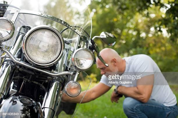 Older man repairing motorcycle in park