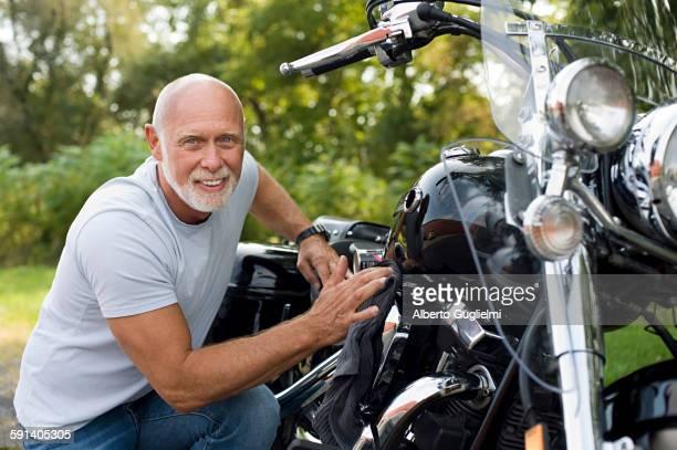 Older man repairing motorcycle