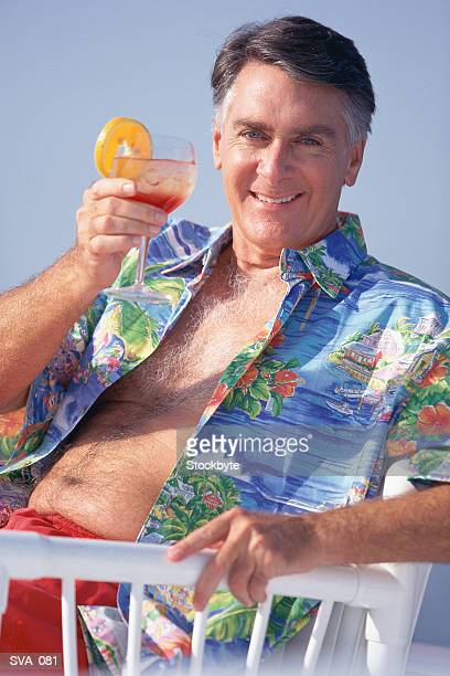 Older man sitting in chair, holding up cocktail glass, smiling