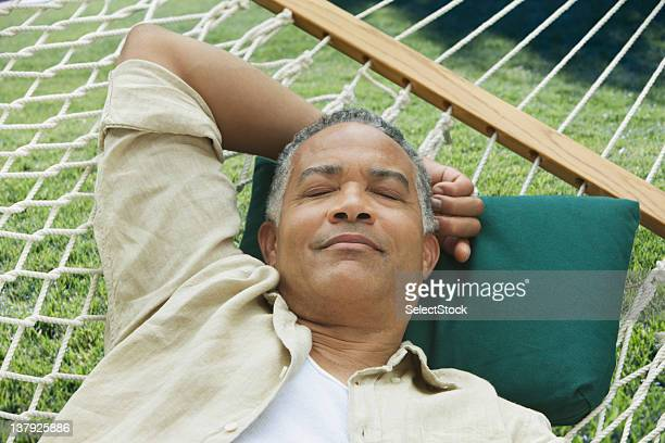 Older man sleeping on a hammock