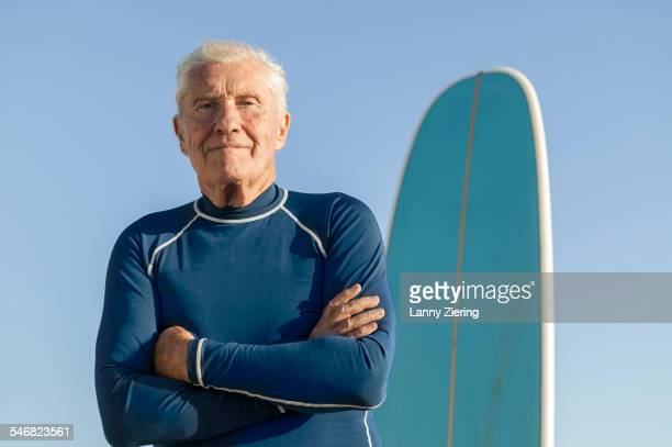 Older man standing near surfboard outdoors