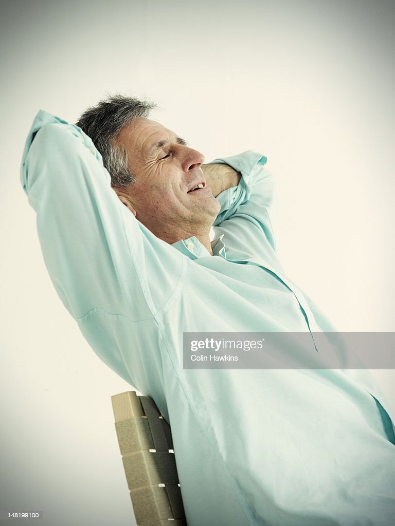Older man stretching in chair : Stock Photo