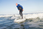 older man surfing a long long board