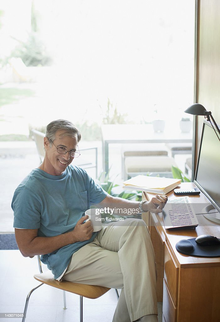 Older man using computer indoors : Stock Photo