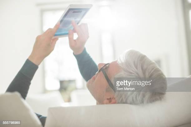 Older man using digital tablet in living room