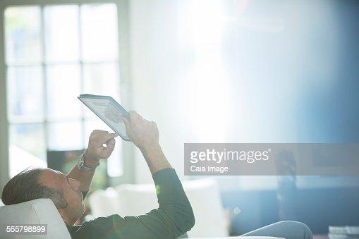 Older man using digital tablet on sofa
