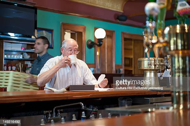 Older man using tablet computer in cafe