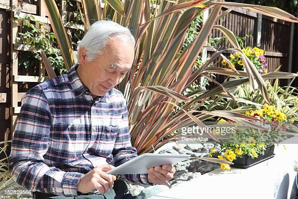 古い男性のタブレットコンピューターを使用して屋外