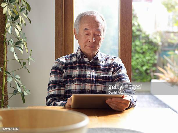 Older man using tablet computer