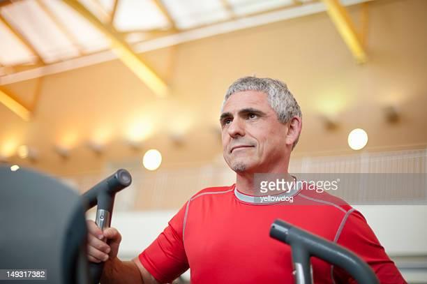 Older man using treadmill in gym