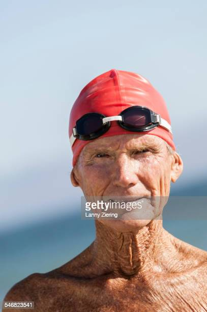 Older man wearing swimming cap and goggles outdoors