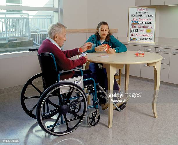 Older man with a disability playing cards with his friend.