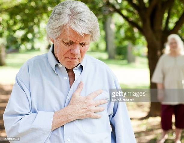 Older man with a hand over his chest in pain