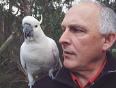 Older man with cockatoo on his shoulder