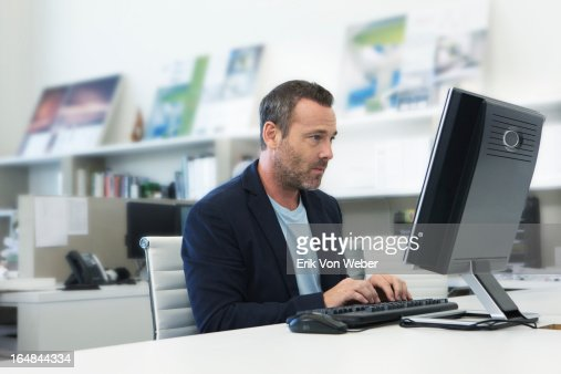 older man working on computer in small modern offi : Stock Photo
