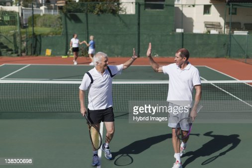 Older men high-fiving on tennis court