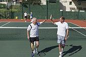 Older men high-fiving on tennis court