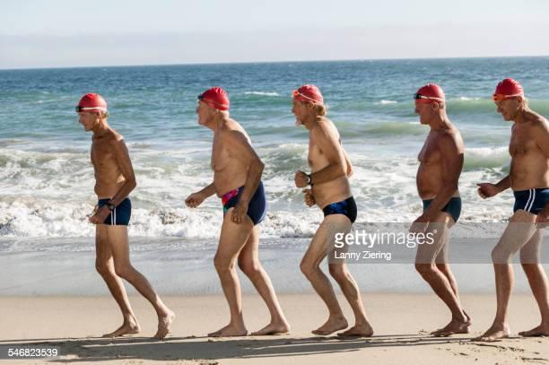 Older men on swimming team running on beach
