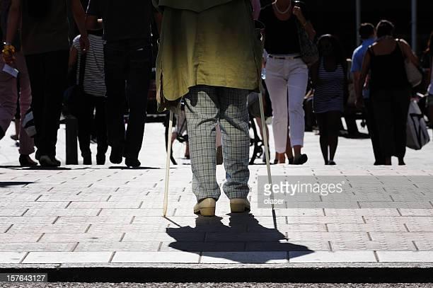 Vecchio persona con bastoni da passeggio, accanto a Traversata di zebra