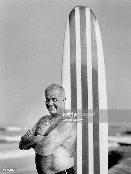 Older proud man with surfboard