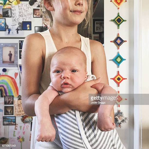 Older sibling holding onto curious infant