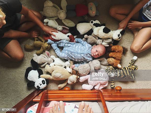 Older siblings playing with infant on the floor