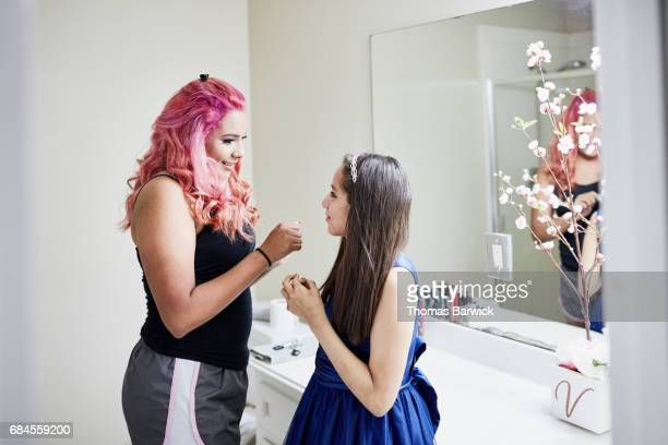 Older sister helping younger sister prepare for quinceanera in bathroom