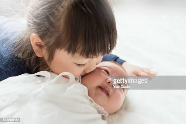 Older sister kissing her sister's baby.