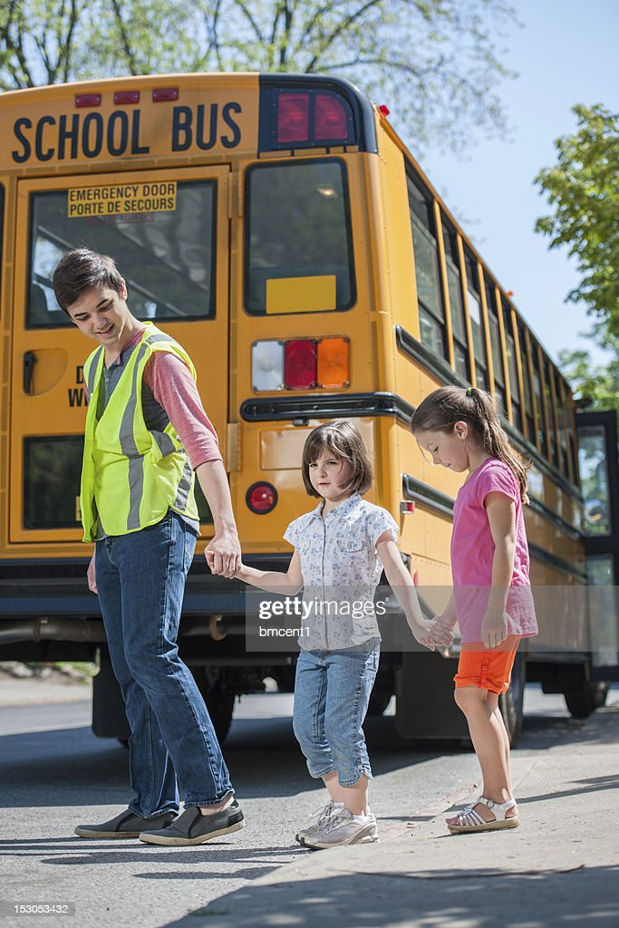 Older Student Crossing Guard Helps Young Elementary Students : Stock Photo