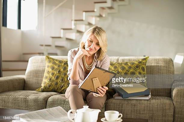 Older woman admiring framed photos