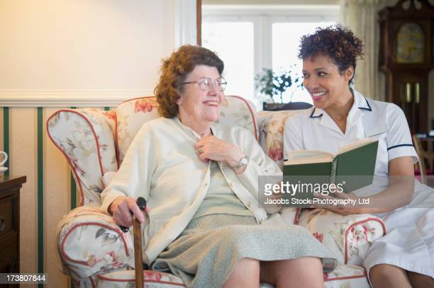 Older woman and caretaker reading together