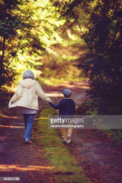 older woman and child walking down mossy road