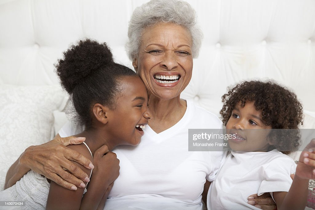 Older woman and grandchildren hugging : Stock Photo