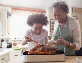 Older woman and granddaughter cooking together in kitchen