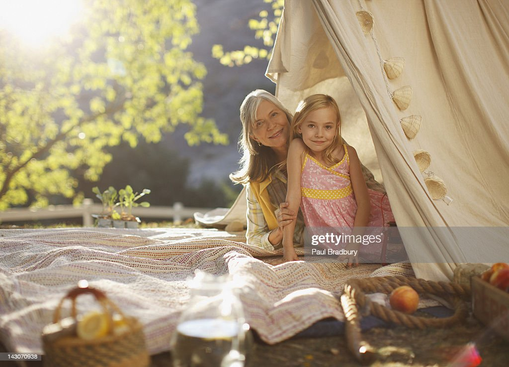 Older woman and granddaughter sitting in tent : Stock Photo
