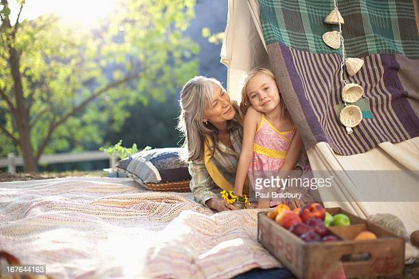 Older woman and granddaughter sitting in tent