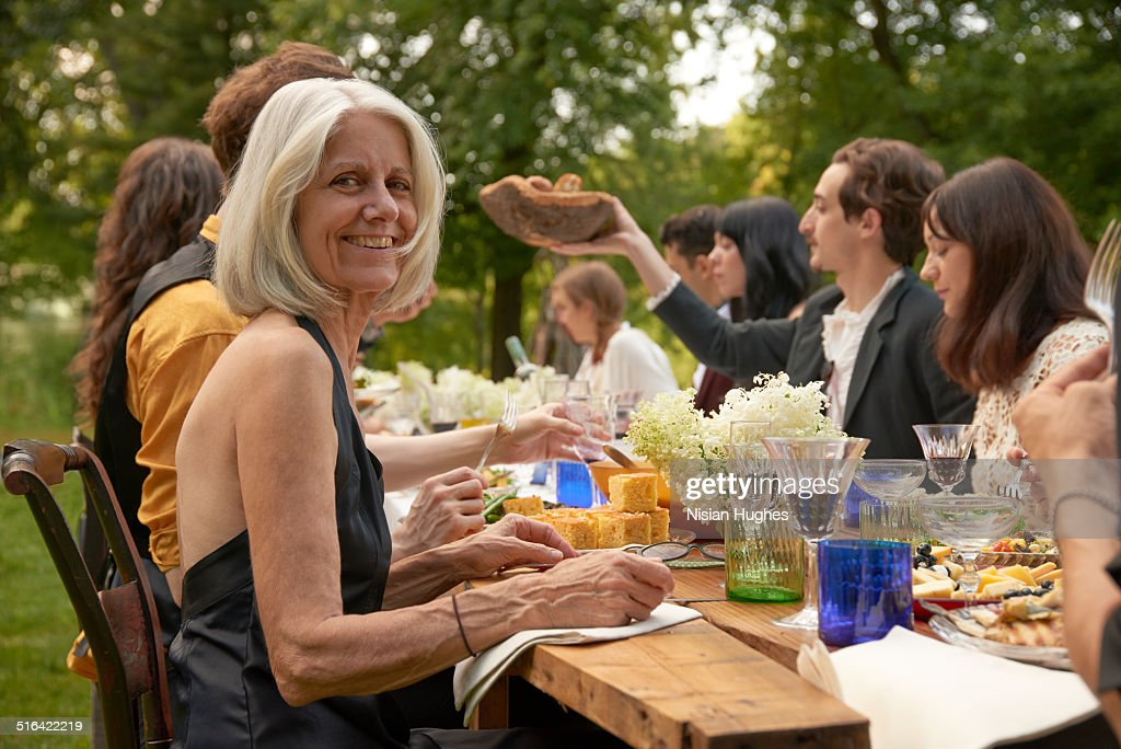 Older woman at outdoor dinner party with friends