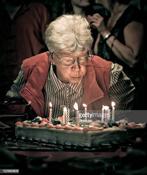 Older woman blows out birthday candles