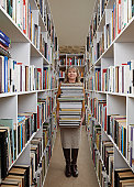 Older woman carrying books in library
