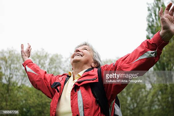Older woman cheering in park