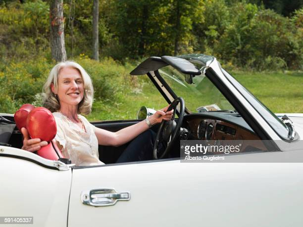 Older woman driving convertible in park