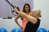 A beautiful young fitness instructor helps the older lady in exercise